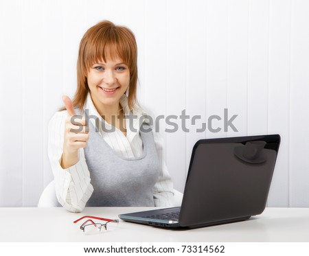 Positive smiling businesswoman with a laptop with a thumb up - stock photo