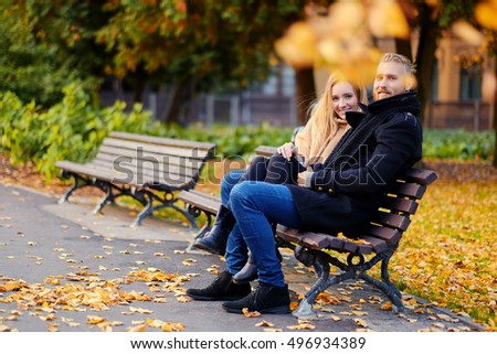 Positive smiling couple of redhead male and blonde female relaxing on a bench in an autumn city park.