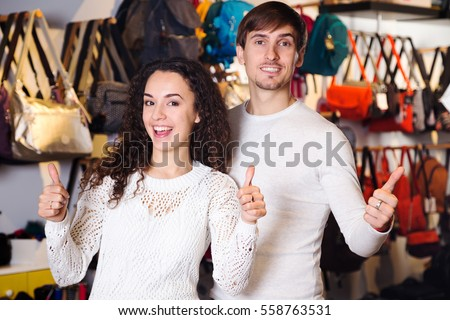Positive smiling family in store of hanbags