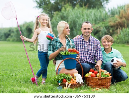 Positive smiling family with two children at summer picnic at the lawn