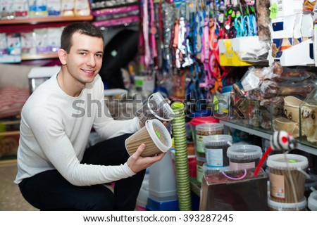 Positive smiling guy buying chewable sticks and bones for pets 