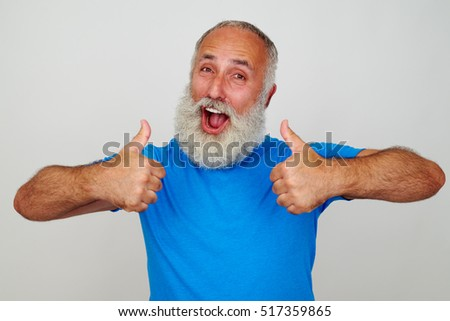 Positive smiling man with white beard opened his mouth in delight and is giving two thumbs up against white background