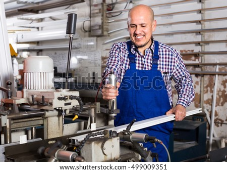 Positive smiling middle-aged man in coverall toiling on a machine in PVC shop