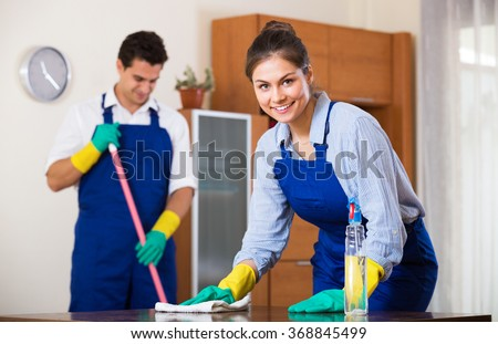 Positive smiling  professional cleaners doing cleanup in ordinary apartment - stock photo