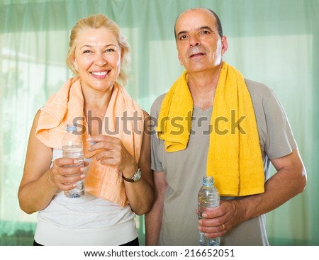 Positive smiling senior couple drinking water after fitness at home  - stock photo