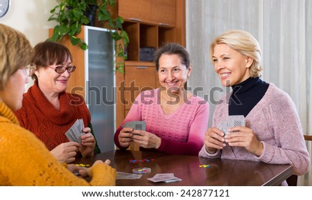 Positive smiling senior female friends staking money during bridge - stock photo