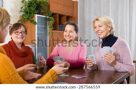 Positive smiling senior women playing cards at home - stock photo