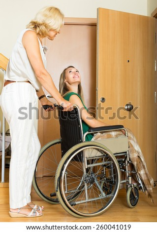 Positive social worker and disabled young woman on chair returning home - stock photo