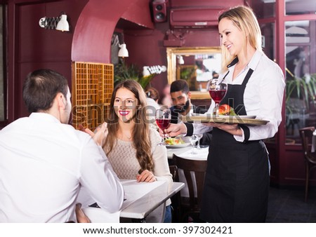 Positive spanish waitress serving meal for young couple at table