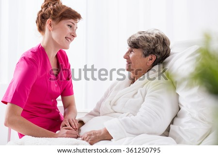 Positive talking to senior patient in hospital - stock photo