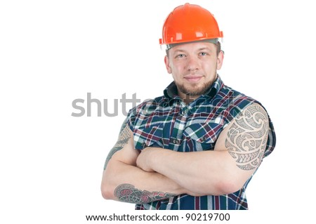 Positive tattooed manual worker in sleeveless work shirt and hardhat with his arms crossed, white background - stock photo