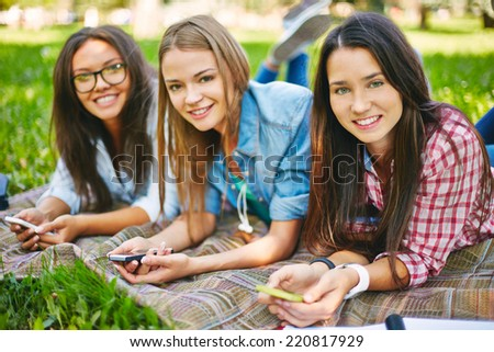 Positive teenage girls with telecommunication technologies looking at camera in park - stock photo
