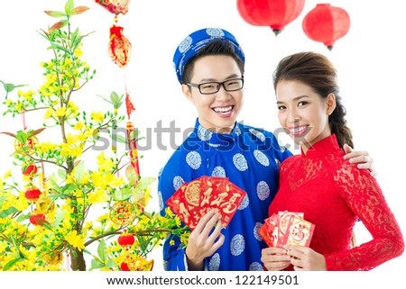 Positive Vietnamese couple with red envelopes for Tet - stock photo