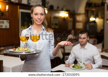 Positive waitress holding tray with glasses of wine in bar  - stock photo