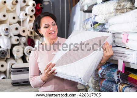 Positive woman customer handles bedspread near textiles shelves inside - stock photo