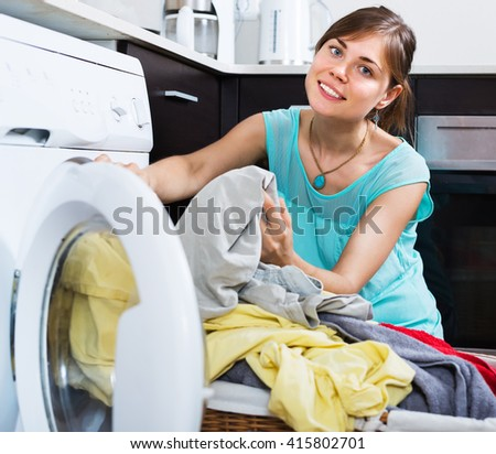 Positive woman enjoying clean clothes without stains after laundry
