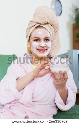 Positive woman in bathrobe putting cosmetic treatment on face in flat - stock photo