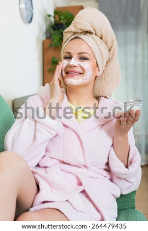 Positive woman in bathrobe putting cosmetic treatment on face in house - stock photo