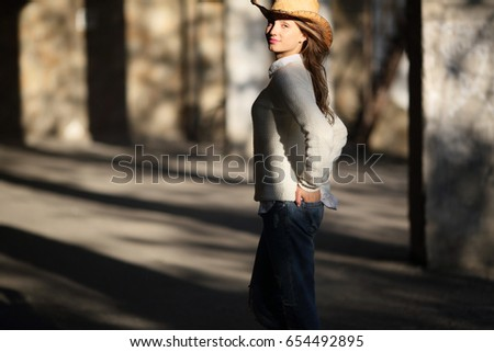 Positive woman modern cowboy with hands in back pockets, standing, turn, outdoor, urban background