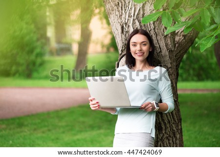 Positive woman standing under the tree
