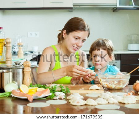 Positive woman with a girl cooking red fish dumplings together at home kitchen
