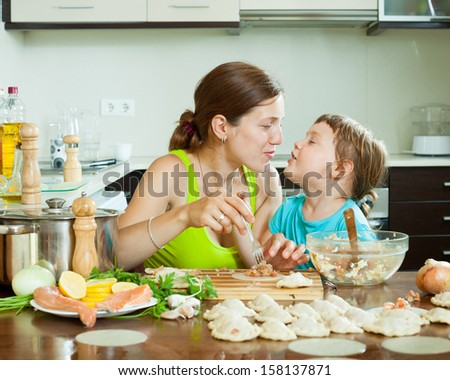 Positive woman with girl cooking fish dumplings together  at home kitchen