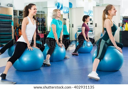 positive women jumping on exercise ball during group train - stock photo