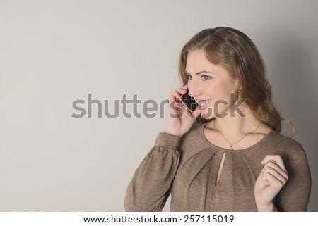 Positive young blonde woman talking on the phone