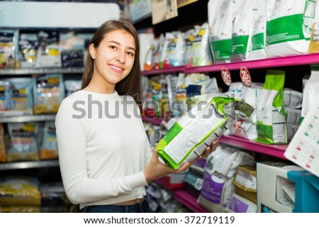 Positive young brunette carefully choosing dry food fore home pet - stock photo