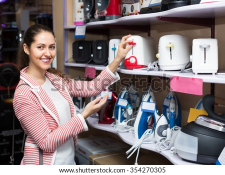 Positive young brunette choosing pop-up toaster in hypermarket and smiling