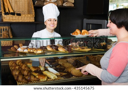 Positive young cook gladly selling pastry to a customer in the cafeteria