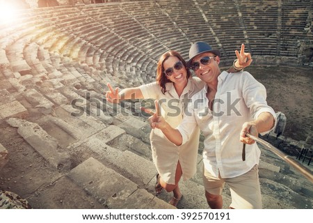 Positive young couple take selfie photo in Side antique amphitheater - stock photo