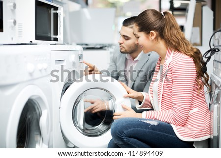Positive young family couple buying new clothes washer in supermarket. Focus on the woman