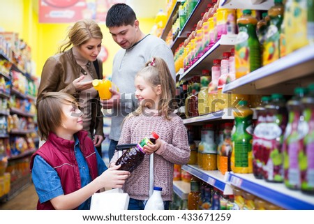 Positive young family of customers with children purchasing carbonated beverages