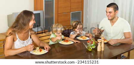 Positive young family of four eating spaghetti at home interior. Focus on woman
