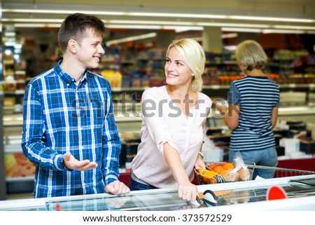 Positive young family standing near display with frozen food in supermarket. Focus on the woman - stock photo