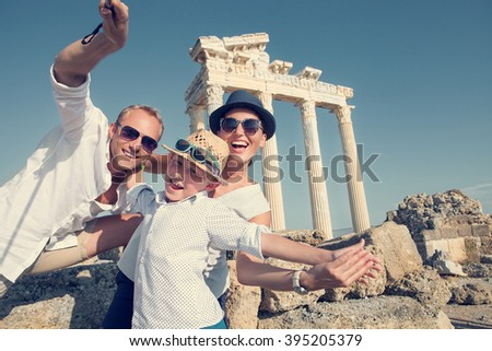 Positive young family take a sammer vacation selfie photo on antique sights view - stock photo