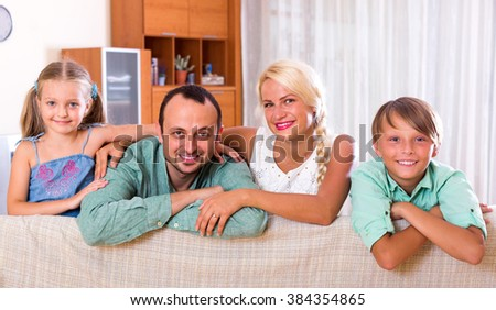 Positive young family with two kids on couch indoors - stock photo