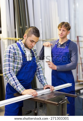 Positive young males working together on a machine in modern factory - stock photo