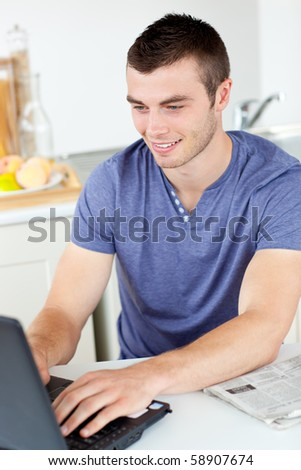Positive young man using his laptop in the kitchen at home - stock photo