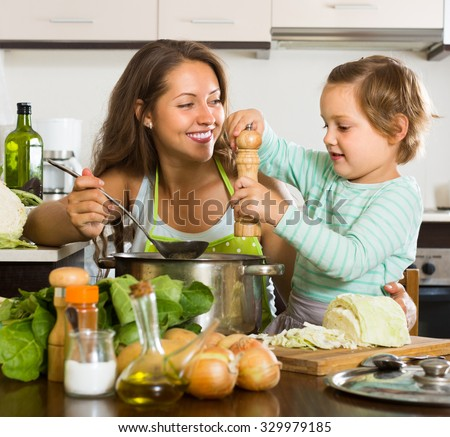 Positive young mother with little daughter cooking at home kitchen - stock photo