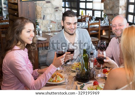 Positive young people enjoying a food and smiling at tavern  - stock photo