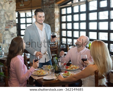 Positive young people enjoying a food and smiling in tavern  - stock photo
