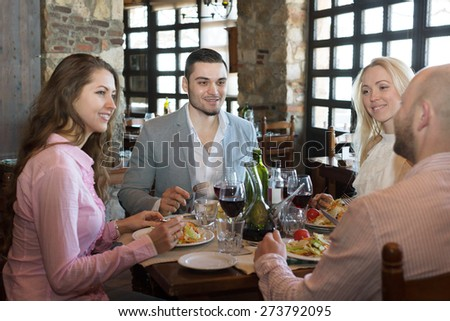 Positive young people enjoying food and smiling at tavern  - stock photo