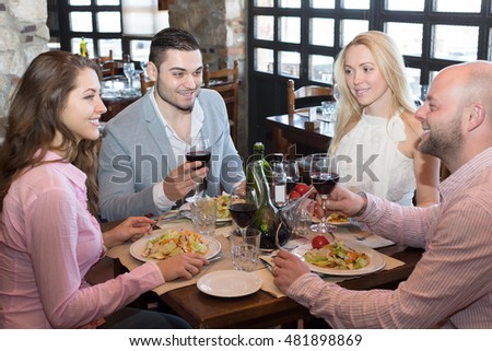 Positive young people enjoying food and smiling in tavern