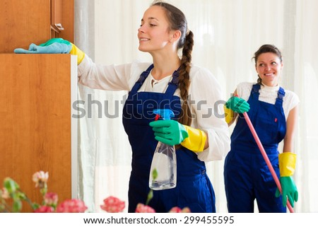 Positive young professional cleaners woman washing apartment with rag and mop - stock photo