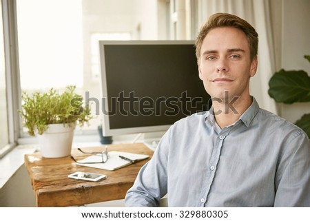 Positive young professional sitting in a neat office space for one with a plant on his desk next to his computer - stock photo