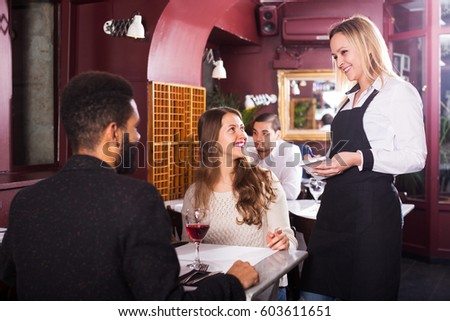 Positive young spouses having date in middle class restaurant