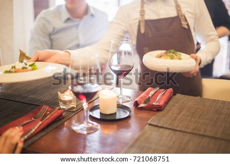Positive young waiter serving terrace restaurant guests at table.