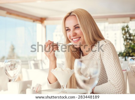 Positive young woman eating ice cream in light summer cafe
